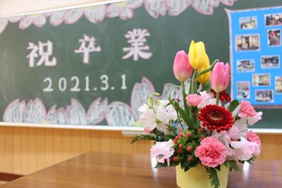 教室の黒板アート「祝卒業」と教卓の花