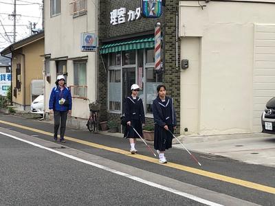 白杖を振って歩道を歩行している様子