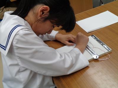 点字盤で点字を書く様子
